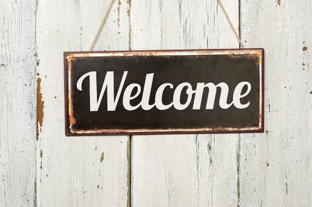 Foto per Old metal sign in front of a white wooden wall - Welcome - Immagine Royalty Free