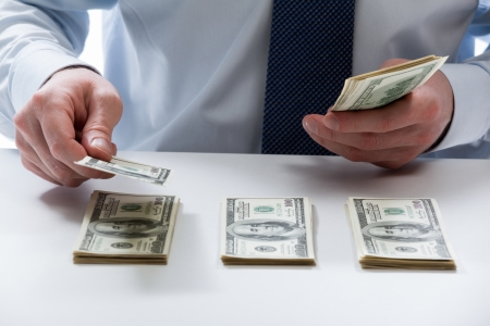 Photo pour Bank teller's hands counting dollar banknotes on the table - image libre de droit