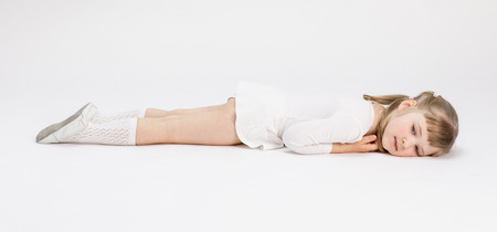 Beautiful little girl resting on the floor, white background
