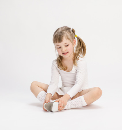 Pretty little girl sitting on the floor and doing exercise, white background