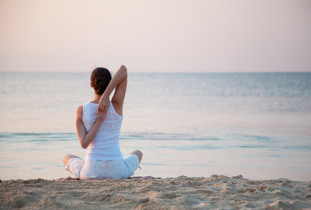 Photo pour Young woman doing exercises sitting on sea coast at dawn - image libre de droit
