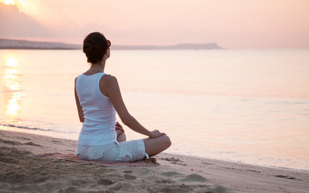 Photo pour Young woman meditating on the sea coast at dawn - image libre de droit