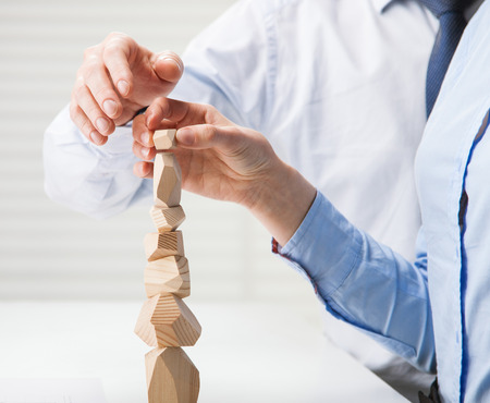Foto de Business people building wooden tower (Japanese game tumi-ishi), illustrating concept of business success, cooperation, achievement and self-control - Imagen libre de derechos