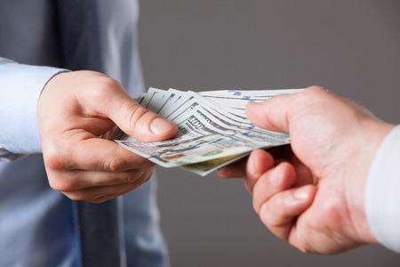 Foto de Human hands exchanging money on blue background, closeup shot - Imagen libre de derechos