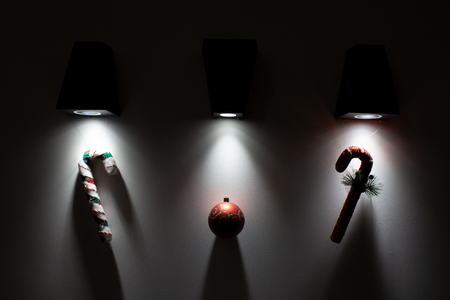 Foto de Christmas decorative decorations are illuminated from beneath from above by lamps on a background a wall - Imagen libre de derechos