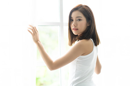 Photo pour Young joyful Asian woman turn back and holding the curtains open to look out of large light window at home, turning to look and smile at camera. - image libre de droit
