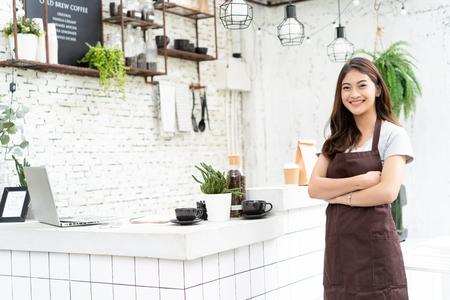 Foto de Attractive young Asian beautiful caucasian barista in apron smiling at camera in coffee shop counter. Startup Business Owner Concept. - Imagen libre de derechos