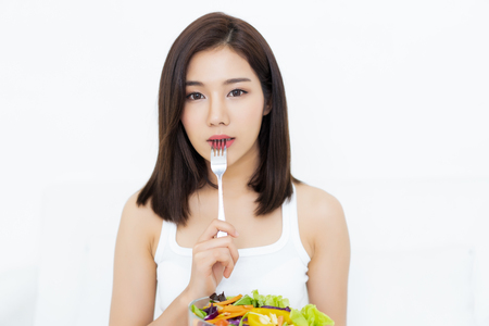 Photo pour Portrait of young Asian woman eating healthy salad and pressing fork to her lips and looking at camera isolated on white white background - image libre de droit