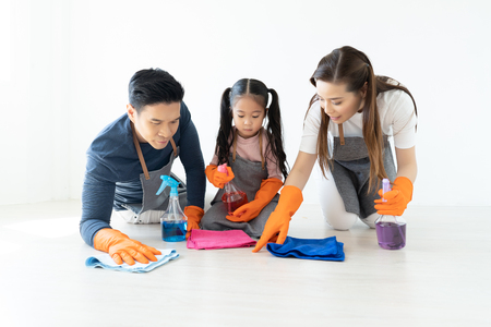 Foto de Happy young Asian family of three cleaning their home living room at weekend.Cute little helper. Family housework and household concept. - Imagen libre de derechos