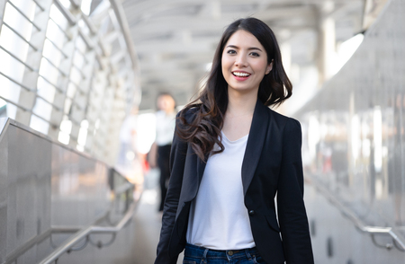 Foto de Young elegant business woman looking at camera and walking along sidewalk outdoors in urban city ,business trip,travel. - Imagen libre de derechos
