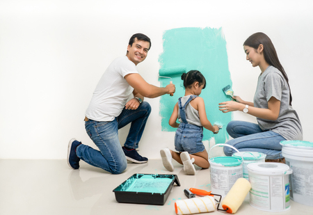 Foto de Happy family renovating their new home.Father sitting near daughter, smiling painting with a roller and looking at camera. - Imagen libre de derechos
