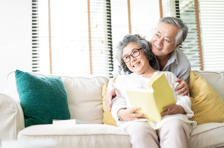 Foto de Happy senior couple are sitting on the couch together and reading a book and looking sideways in living room at home. - Imagen libre de derechos