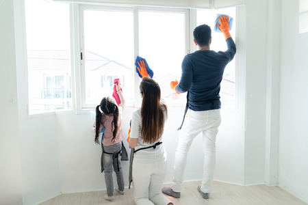 Foto de Back view of Asain family doing the house cleaning. Young family washing windows together in living room. Family housework and household concept. - Imagen libre de derechos