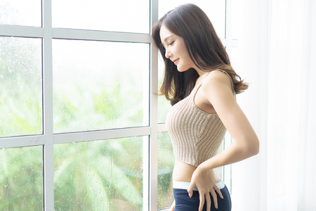 Photo for Portrait of a young joyful Asian woman looking through glass window with raindrops at her home. Lifestyle and Relax Concept. - Royalty Free Image