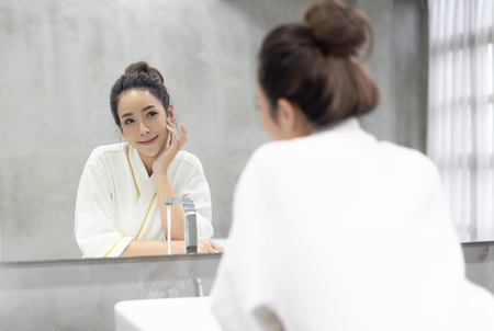 Photo pour Facial Beauty.Beautiful smiling young Asian woman in bathrobe applying moisturizer cream on her pretty face and looking to mirror at bathroom, touching face with hands . Natural skin care and people Concept. - image libre de droit