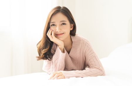 Photo for Portrait of young Asian woman smiling friendly and looking at camera in living room.Woman's face closeup. Concept woman lifestyle and winter. Autumn, winter season. - Royalty Free Image