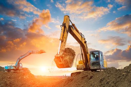 Foto de excavator in construction site on sunset sky background - Imagen libre de derechos