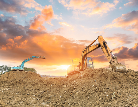 Foto per Excavator working at construction site on sunset - Immagine Royalty Free