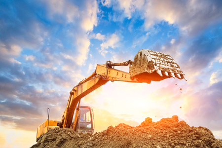 Photo pour Excavator working at construction site on sunset - image libre de droit
