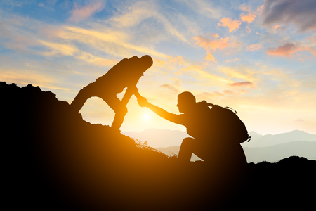 Foto de people helping each other hike up a mountain at sunrise,giving a helping hand,concept scene - Imagen libre de derechos