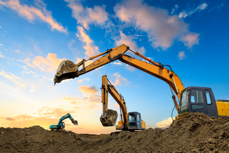 Photo pour Three excavators work on construction site at sunset - image libre de droit