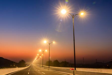 Photo pour City road and bright street lights landscape at sunset - image libre de droit