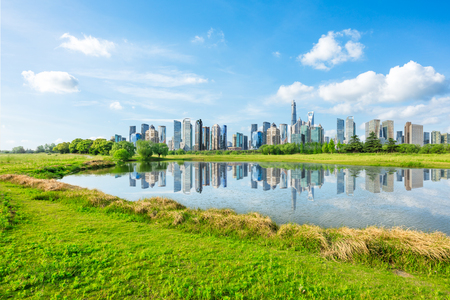 Photo pour Shanghai city skyline and green grass with lake under the blue sky,China - image libre de droit