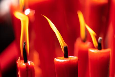 Foto de Rows of burning red candles are used in religious prayers - Imagen libre de derechos