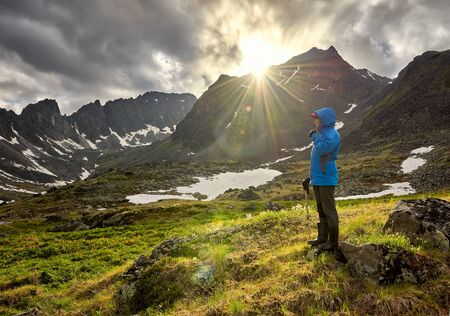 Photo pour Pass hopping. Woman stands on mound in mountain tundra on cold morning. The sun's rays beautifully illuminate space next to girl - image libre de droit