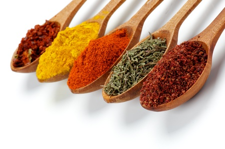 Photo for Arrangement of Spicy Spices with Ground Sumach, Oregano, Dried Paprika, Curry and Crushed Chili in Wooden Spoons isolated on white background - Royalty Free Image