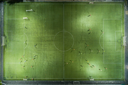 Foto de Football players running around the football field. Night workout. Preparation for the match.  Aerial shot with a drone from a altitude - Imagen libre de derechos