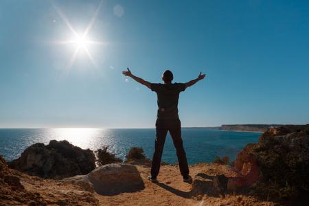Foto de Arms raised man standing on the cliff in front of Atlantic ocean. - Imagen libre de derechos