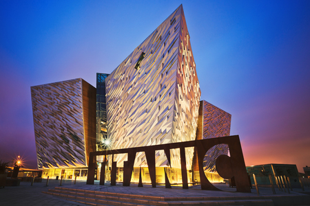 Foto de BELFAST, NORTHERN IRELAND - JUNE 28, 2017: Sunset over Titanic Belfast - museum, touristic attraction and monument to Belfasts maritime heritage on the site of the former Harland and Wolff shipyard. - Imagen libre de derechos
