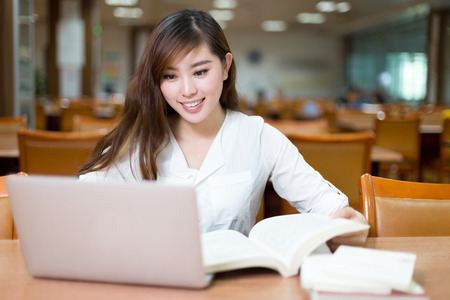 Photo for Asian female student studying in library with laptop - Royalty Free Image