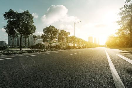 Foto de empty asphalt road with trees under sunshine - Imagen libre de derechos