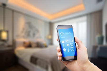 Foto per mobile phone with apps on smart home in modern bedroom - Immagine Royalty Free