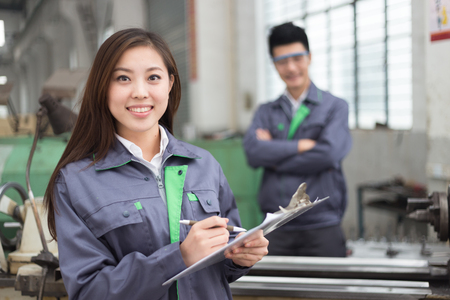 Photo for young chinese man and woman work in motor manufacturing factory - Royalty Free Image