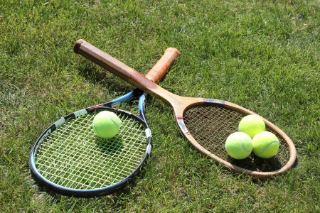 Vintage and new tennis rackets with balls on grass court