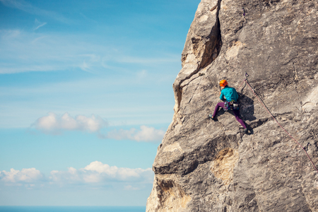 Foto de The girl climbs the rock against the sky. The climber in helmet trains on a natural relief. Extreme sport. Active recreation in nature. A woman overcomes a difficult climbing route. - Imagen libre de derechos
