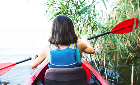 Photo for girl in the kayak swims through the jungle. a trip across the river through the jungle and thickets of grass. - Royalty Free Image