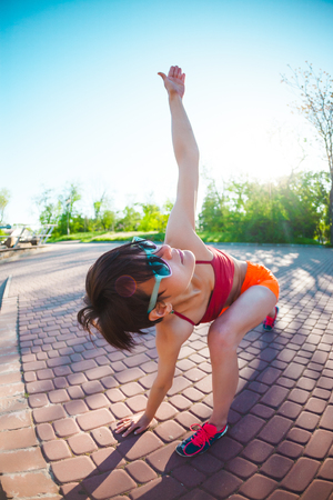 Photo pour Yoga in the streets of the city. A girl is doing exercises at dawn. A woman is training in the park. Brunette meditates in nature. Quiet place for training in a bustling city. - image libre de droit