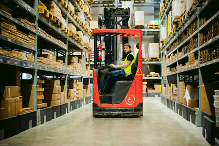Photo pour young man in working clothes, driver Reachtruck busy working on the logistics warehouse store - image libre de droit