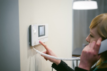 Foto de blonde woman answers the intercom call while holding the phone to your ear - Imagen libre de derechos