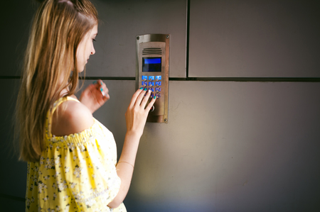 Photo for woman dials an apartment code on an electronic doorphone panel - Royalty Free Image