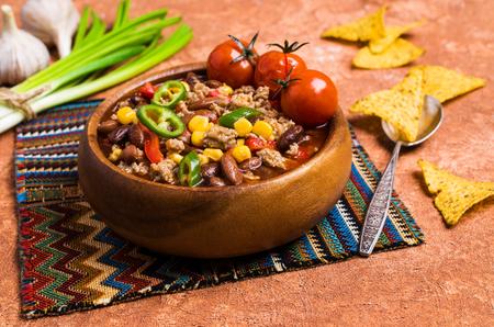 Foto de Traditional Mexican chili con carne on the table with vegetables and nachos. Selective focus. - Imagen libre de derechos