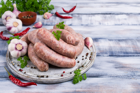 Foto de Thick meat sausages in a natural shell with spices on a wooden background. Selective focus. - Imagen libre de derechos
