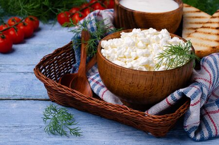 Photo for Granulated white cottage cheese with vegetables and sour cream in a dish on a wooden background. Selective focus. - Royalty Free Image