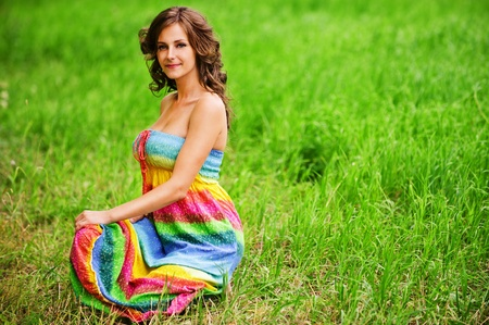 Portrait of young beautiful brunette woman wearing colourful bright dress, sitting on grass at summer green park.
