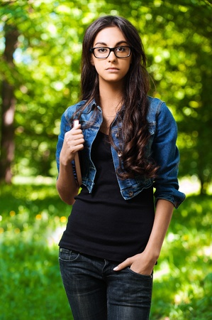 beautiful young woman standing serious park glasses book underarm