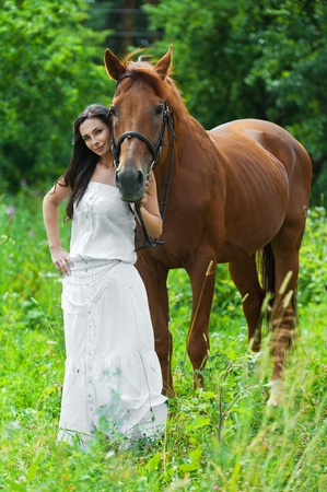 pretty young woman long-haired long white dress next horse